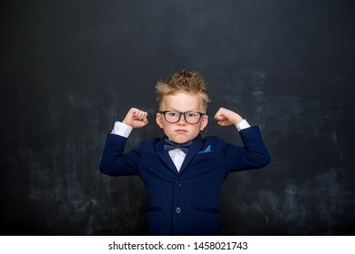 Strong child with muscles on chalkboard dreams to be a businessman.