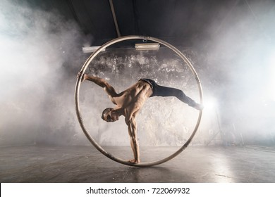 Strong circus performer spinning in the cyr wheel