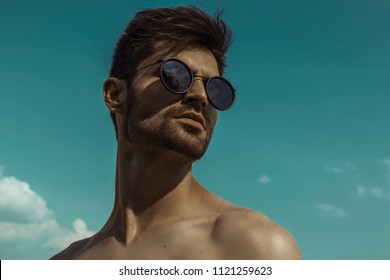 Strong commercial face male model  wearing eyewear on blue sky with clouds