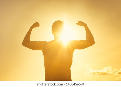 Strong confidant man flexing on sunset background.  Victory, fitness, and determination