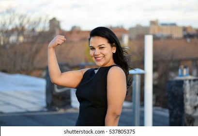 Strong confident hispanic business woman flexing outside