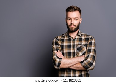 Strong, confident, strict man in casual checkered shirt cross arms over chest and look at camera isolated on gray background with copy space for text