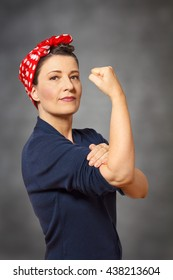 Strong and confident woman with a  red headscarf and a clenched fist, vintage or retro effect of the 40s in America, gray background, copyspace