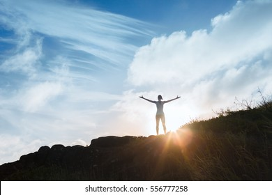 Strong and confident woman standing on top a mountain with arms in the air.