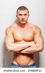 Strong and confident. Confident young shirtless man looking at camera and keeping arms crossed while standing against grey background