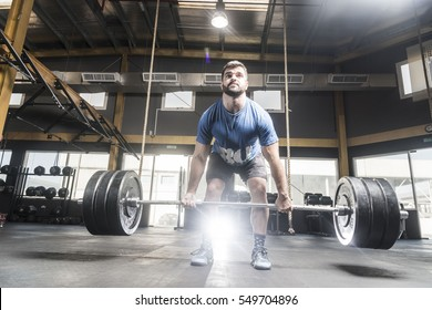 Strong crossfit powerlifter athlete in the process of lifting deadlifting  heavy barbell