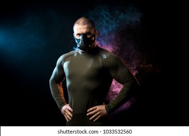 A strong dark-haired sportman  in a green sports shirt and trainig mask posing  against a blue and red vape smoke background on a black isolated