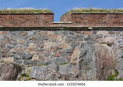 Strong defensive stone wall with grass-topped brick castellation on the fortress island of Suomenlinna, Finland