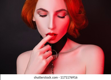 Strong desire for pleasure. Attire for bdsm games. Redhead fetish girl on black. Kinky model with open mouth. Lady with bondage on neck. Sexual bdsm toy for fetish. Feel desire. Kinky woman