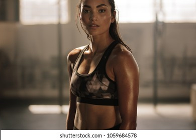 Strong and determined female in sportswear standing in the gym and looking at camera. Sportswoman after intense crossing training workout session in gym.