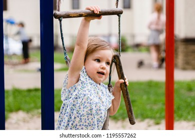 Strong and determined girl climbing a ladder on a playground. Girl power concept, gender equality