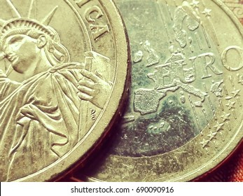Strong dollar - weak euro A dollar piece with the liberty statue in cutout lies over a euro piece in the background