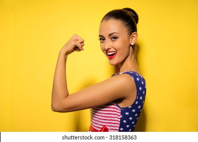 Strong and energy. Pretty young brunette woman showing bicep on her arm. Colorful studio portrait with yellow background.