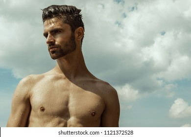 Strong face commercial wet male model on the cloudy sky background