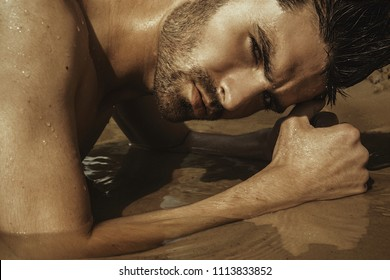 Strong face male model on the nature background with sand and water on the beach on the sunset