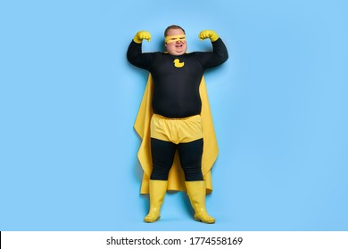 strong fat caucasian superhero man shows his muscles at camera, young male in yellow wear has powerful energy, save the universe