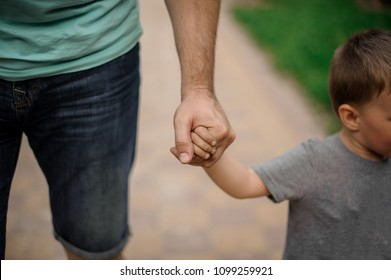 Strong father hand holding a little hand of his son walking down the street on warm day