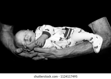 Strong Father Holding Tiny Newborn in His Hands