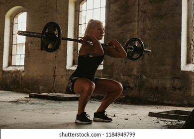 Strong female athlete in lowest front squat position