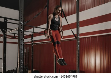 Strong female athlete practicing calisthenics, doing ring dips. Crossfit woman working out on gymnastic rings at the gym.