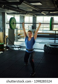 Strong female athlete wearing weightlifting belt doing clean and jerk exercise with barbell during cross training in gym