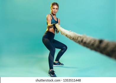 Strong female athlete working out with battling rope at studio. Healthy woman pulling battle rope over blue background.