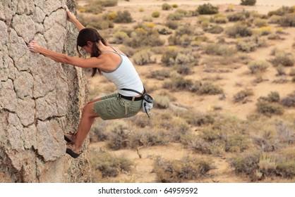 A strong female climber ascends a rock face near Bishop California.