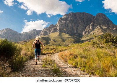 A strong female trail runner with majestic mountains and blue sky