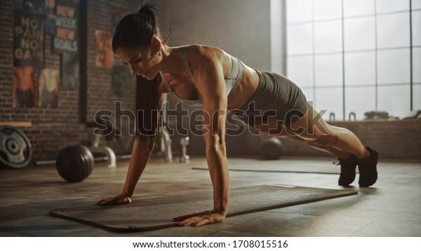 スポーツトップやショートパーツの強くて体に合った運動選手が、人を動かすポスターとロフトスタイルの工業体育館で、押し上げ運動をしている。彼女のフィットネストレーニングの一環だ。暖かい光。