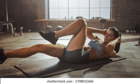 Strong and Fit Beautiful Athletic Girl in Sport Top and Shorts is Doing Crisscross Crunch Workout in a Loft Style Industrial Gym with Motivational Posters. It's Her Fitness Training Program.