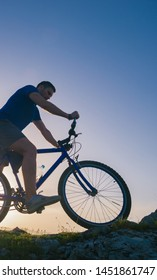 Strong fit male mountain biker performing stunts on rocky terrain on a sunset while wearing a blue shirt and riding a blue bike