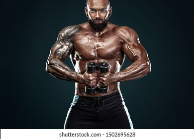 Strong and fit man bodybuilder. Sporty muscular guy with dumbbells. Spot and fitness motivation.
