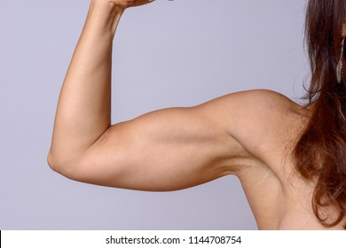 Strong fit mature woman clenching her fist and flexing her arm muscles showing off her toned biceps over a grey background