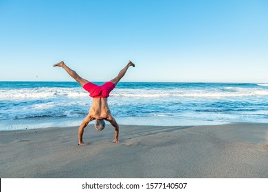 A strong fit muscled mature man in colorful shorts doing handstands or cartwheel on the beach, freedom and healthy lifestyle concept, ocean background with copy space