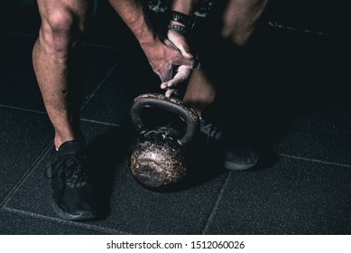Strong fit muscular man with muscles holding heavy kettle bell with his hand on the gym floor prepared for cross strength and conditioning training and workout