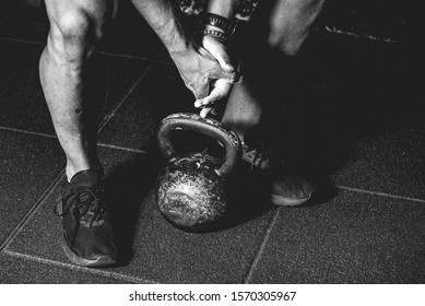 Strong fit muscular man with muscles holding heavy kettlebell with his hand on the gym floor prepared for cross strength and conditioning training and workout black and white