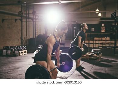 Strong fit people deadlifting barbells. Horizontal indoors shot