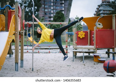 Strong fit woman doing calisthenics exercise in city park.