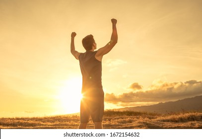 Strong fit young man raising fist up the sunset sky. People victory and triumph.