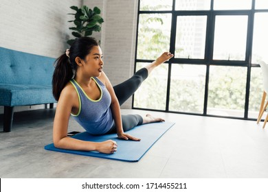 Strong fitness girl in athletic exercise clothes doing a side kick workout while lying down. Asian woman training at home in her living room with cozy sofa home interior setting with copy space