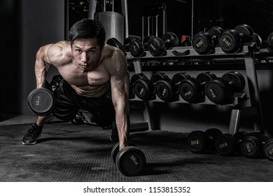 Strong fitness man doing arm workout with dumbbells in the gym