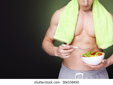 Strong fitness man holding a bowl of fresh salad on dark background