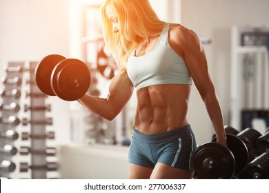 Strong fitness woman bodybuilder with white hair and tanned body pumps up the muscles lifting dumbbells in the gym. Sports and fitness. Fitness woman in the gym. Fitness woman with dumbbell.