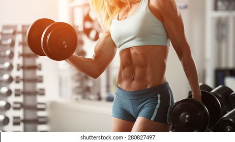 Strong fitness woman bodybuilder with white hair and tanned body pumps up the muscles lifting dumbbells in the gym.  Fitness woman in the gym. Fitness woman with dumbbell. Panorama 16:9
