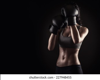 Strong fitness woman in defense position on black background