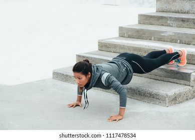 Strong fitness woman workout doing feet elevated push ups and exercising outdoor. Motivated female athlete training strength.