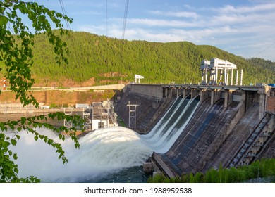 Strong flow of water when discharging water to hydroelectric power station in Krasnoyarsk, Russia. Industrial landscape with open locks on Krasnoyarsk Dam at sunny day.