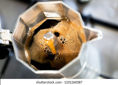 Strong fresh steaming coffe made in Italian style cafetiere. Cloce up, high angle view with selective focus on coffee. Full frame macro crop