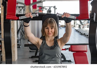 Strong girl athlete trains in the gym