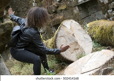 STRONG GIRL CUTING A TREE CUT AND FALLEN IN THE FOREST, ALLEGORICAL SCENE OF NATURE DESTROYED
